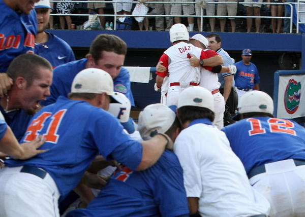 North Carolina State Wolfpack shortstop Chris Diaz gets restrained by coaches after arguing with home plate umpire Steve Corvi after striking out.