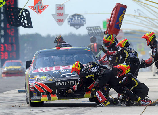Jeff Gordon driver of the #24 DuPont Chevrolet's pit crew changes tires and adds fuel during a pit stop in the 31st Annual Pocono 400 at Pocono Raceway Sunday afternoon.