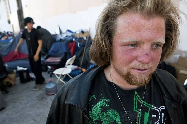 "William Miller, 26, is currently living in a tent with ""If you want peace ,work for justice"" scrawled on the side. Miller says it would be difficult for him to prove that he is a Los Angeles County resident, one of the proposals to reduce fraud and other costs in the general relief program."