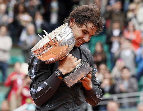 Nadal holds the trophy after his win against Djokovic during their Men's Singles final tennis match during the French Open.