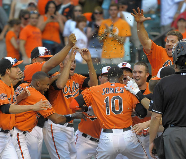 Baltimore Orioles teammates wait to celebrate and mob batter Adam Jones (10), who gets a shower of sunflower seeds as confetti, after his walk-off two-run home run against the Philadelphia Phillies in the 12th inning at Oriole Park at Camden Yards Saturday, Jun 9, 2012. Baltimore beat the Phillies, 6-4, in front of 46,611 fans.