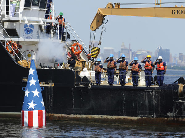 Coast Guard crew onboard the cutter James Rankin salute as Fort McHenry Park Rangers, dressed as 1812 reenactors, fire a two gun salute after the setting of a red, white and blue bouy into the harbor to mark the spot where Francis Scott Key penned the poem that eventually became the National Anthem. The Coast Guard set the first marker in 1914 and every year since 1973.