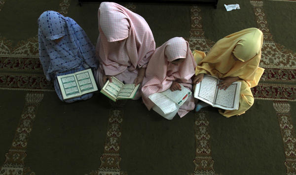 Palestinian girls attend a class on how to read the Koran, Islam's holy book, at a camp in a local mosque in Gaza City.