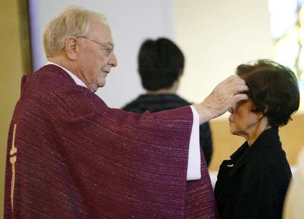 Father Thomas Doyle applies ashes to the forehead of a parishioner at the conclusion of a service on the first day of Lent at the St. James Catholic Church in La Crescenta on Thursday, February 22, 2012.