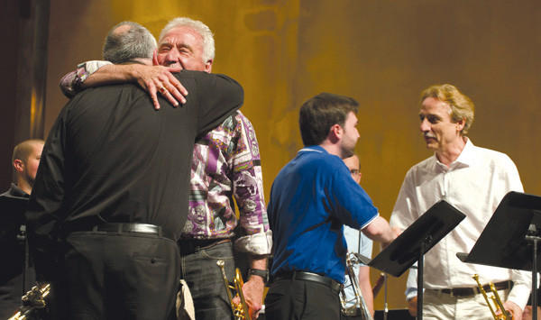 Vincent DiMartino, left, and Doc Severinsen hug after performing Sunday in Newlin Hall during the grand finale of the Great American Brass Band Festival.