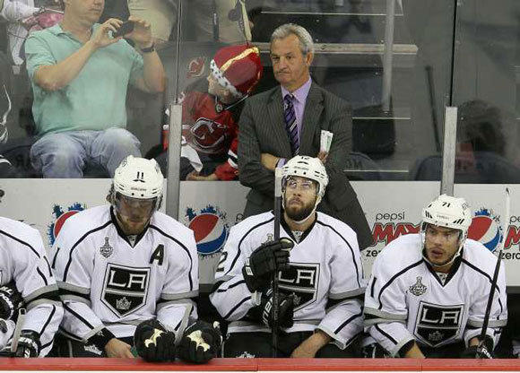 Darryl Sutter stands along the Kings bench (with a little Devil behind him) during Game 5 in New Jersey.