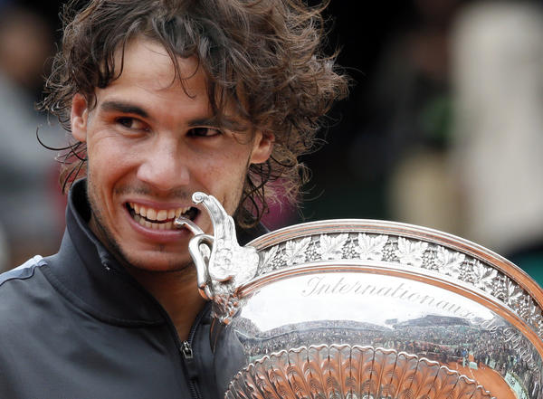 Spain's Rafael Nadal celebrates with his trophy after winning against Serbia's Novak Djokovic their Men's Singles final tennis match during the French Open tennis tournament at the Roland Garros stadium, on June 11, 2012 in Paris.