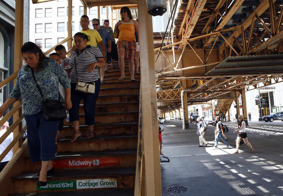 Passengers on Sunday leave the CTA station at Lake and State Streets near where a group of suspects accosted a couple Saturday night.