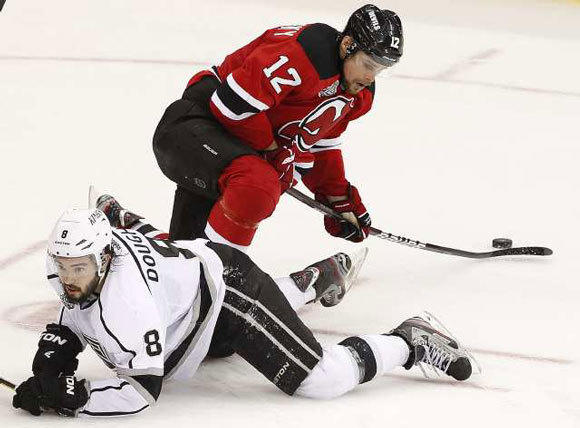 Drew Doughty looks for the puck as Devils winger Alexei Ponikarovsky gathers it in during the third period of Game 5.
