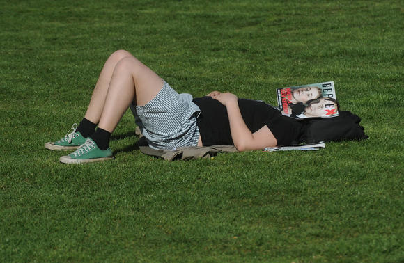 A man sleeps in the grass with a magazine covering his face