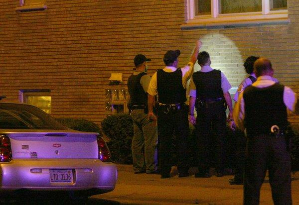 Chicago police examine the hole from a bullet that struck a Southwest Side building and injured a 17-year-old girl.
