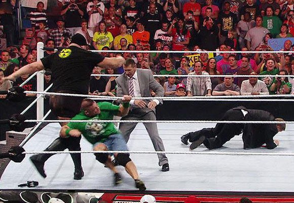 Vince McMahon (wearing the suit) is just moments away from being knocked out by the Big Show.
