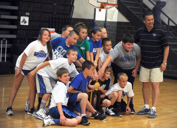 Children get their picture taken with Kentucky coach John Calipari and the Wildcats' national championship trophy Monday during Calipari's satellite camp at Boyle County High School.