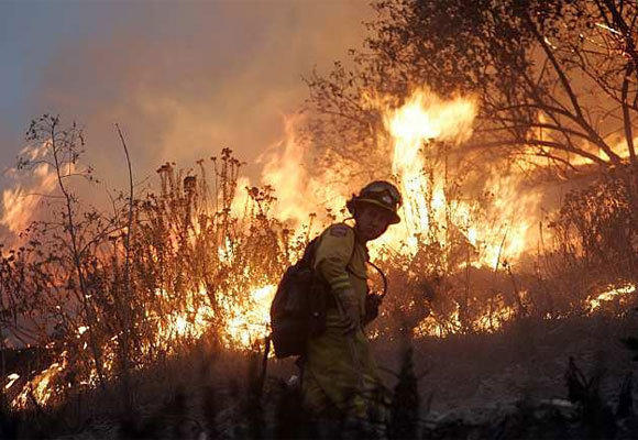 A firefighter watches a backfire set to protect a ranch along Grimes Canyon Road in Ventura County in 2009.