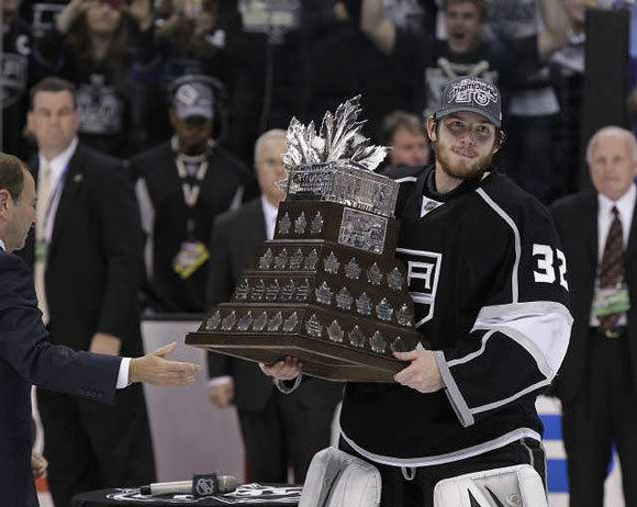 Kings goalie Jonathan Quick holds the Conn Smythe Trophy.