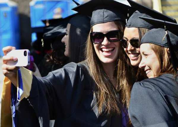 Danielle Gonzalez, left, takes a photo with friends Melissa Cascarano and Abby Arii before commencement ceremonies last month for Fresno State University's Department of Social Work Education, at Woodward Park's Rotary Amphitheater in Fresno.
