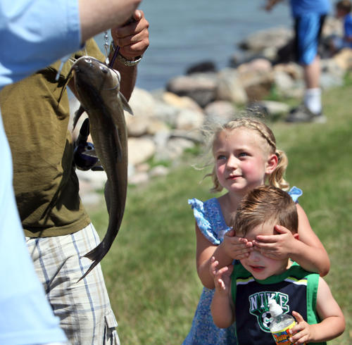 Katelynn Dallmann, 4, covers the eyes of her brother Paxton, 2, as she watches a fish she caught get weighed Saturday during the kids fishing contest at the Family Fun Weekend at Wylie Park. photo by john davis taken 6/9/2012