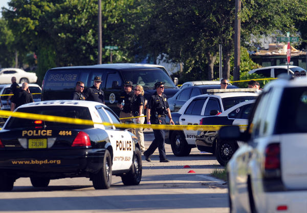 Boynton Beach police gather evidence at the scene of a shooting Tuesday evening along Railroad Avenue near NE 9th Avenue. The shooting left the suspect dead and an officer wounded.