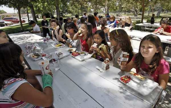 About 50 children enjoy a hot lunch from the summer parks program in 2010. Burbank has cut the program this summer.
