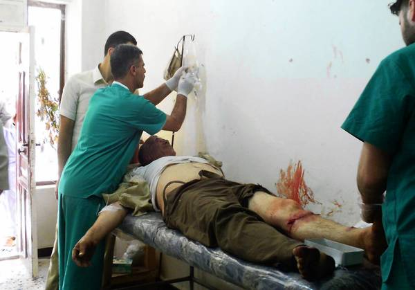 Nurses at the field hospital in Qusair, Syria, treat a man who had just been shot twice in the leg by a sniper.