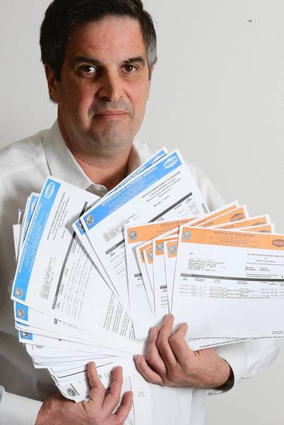 Mark Geinosky in 2009 holds city of Chicago parking tickets fraudulently issued to him. Two of four Chicago police officers recommended for dismissal in the case were found not guilty of being involved, according to a Police Board ruling released Tuesday.
