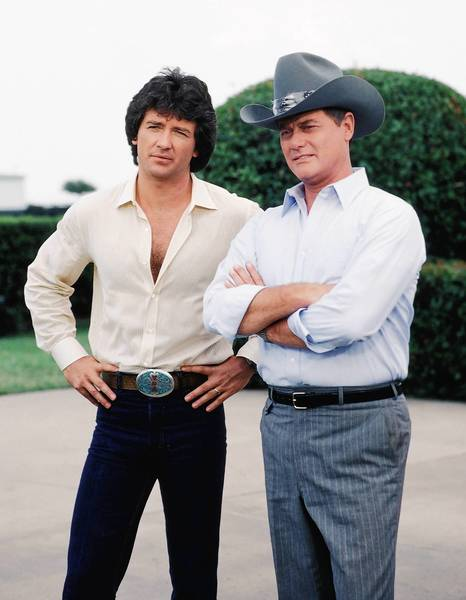 "Patrick Duffy as Bobby Ewing and Larry Hagman as J.R. Ewing Jr. stand together in the early days of ""Dallas."""