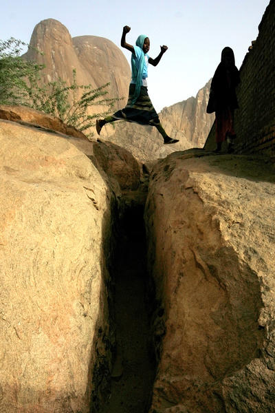A Sudanese girl jumps over a ditch in the eastern Kassala State on June 12, 2012. Sudan has caused frustration among donor countries by ordering seven foreign aid agencies out of its impoverished eastern region.