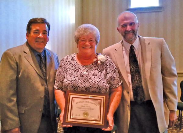 Linda Aleshire, center, is shown at her June 6 retirement dinner with Washington County Public Schools Superintendent Clayton Wilcox, left, and Wayne Ridenour, president of the Washington County Board of Education.