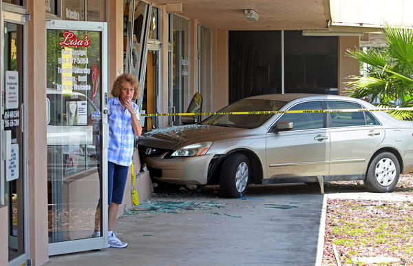 Sharon Litts, a hairstylist at Lisa's Hair Design, looks at the activity surrounding a Margate crash Wednesday that left a vehicle occupant dead.