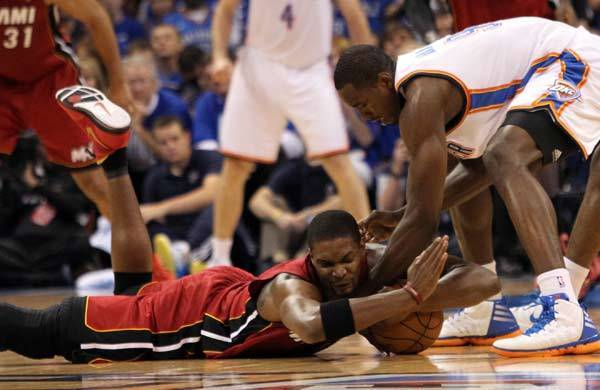 Miami Heat power forward Chris Bosh (1) and Oklahoma City Thunder center Kendrick Perkins (5) battle for a loose ball during the first quarter of game one in the 2012 NBA Finals at the Chesapeake Energy Arena.