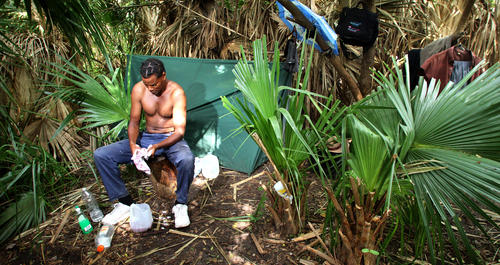 James Ross, a homeless man who is suing local colleges under a little-known state law that says those who lack permanent shelter can attend for free, washes up at his current campsite in a wooded area east of downtown Orlando,  Wednesday, June 13, 2012.