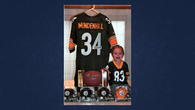 Allyson Van Gilder, daughter of Erin and Jason VanGilder, Berlin, shows the autographed Pittsburgh Steelers items that will be available Friday at the Meyersdale Relay For Life.