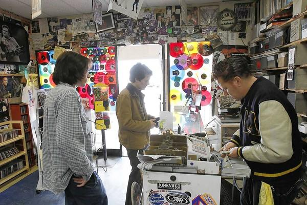 "Darren ""Drak"" O'Connor, right, the owner of Vinyl Solution Records, helps his customers Cory Heskett, left, and Patrick Pescador at his store in Huntington Beach on June 4."