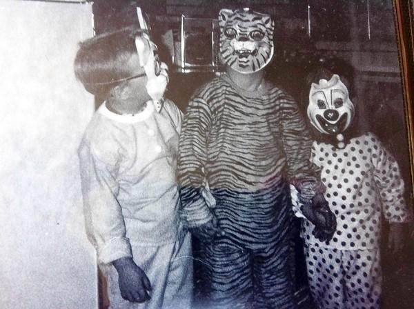 Tom Burick, the tiger in the middle, holds hands with his younger brothers in a family Halloween photo. He says one of them recently told him he had been sexually abused, too.
