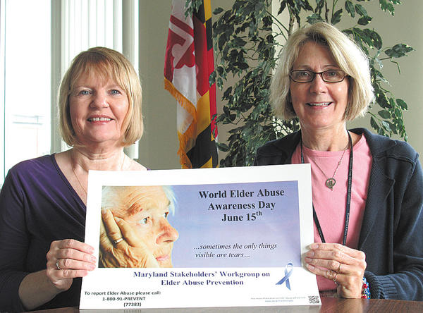 From left, Jeannie Huntzberry, volunteer ombudsman, and Lynn Smith, Washington County Commission on Aging ombudsman, display a poster designating June 15 as World Elder Abuse Awareness Day.