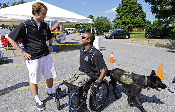 Boys' Latin graduate Tyler Steinhardt, left, who organized the Shootout for Soldiers event, talks with U.S. Army Staff Sgt. Ryan Major, of Towson, who was wounded in Iraq in 2006. Major and his dog, Theodore, helped promote the 24-hour lacrosse event to benefit the Wounded Warrior Project, which assists wounded members of the U.S. military such as Major.