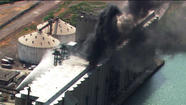 Firefighters shoot water at a grain silo on fire on Lake Calumet this afternoon. WGN-TV