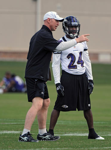 Ravens special teams coordinator Jerry Rosburg talks with Corey Graham during the final practice of the three-day minicamp.