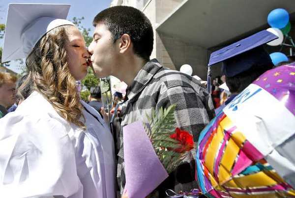 Krystal Griffin gets a kiss from her boyfriend, Oscar Hernandez, after the Re-connectEd Glendale graduation at the First United Methodist Church Carlson Fellowship Hall.