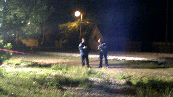 Chicago police working inside a crime scene behind a home where a police officer was shot early Friday morning.