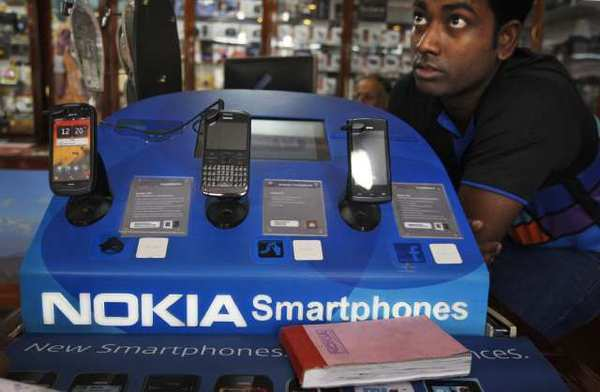 An Indian shopkeeper selling Nokia mobile phones awaits customers in New Delhi. Moody's cut Nokia's rating to junk on Friday