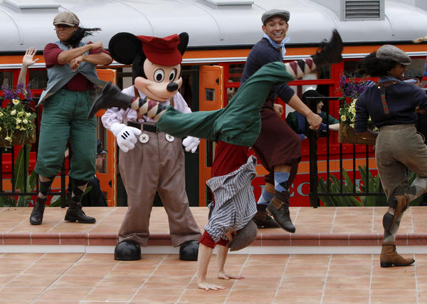 "Disney cast members portraying characters from the film and Broadway stage musical ""Newsies"" dance with  Mickey Mouse during the opening ceremonies for Cars Land at Disney California Adventure."