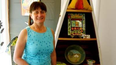 Louise Hopson stands near a display of artwork at the Art Cats Gallery location which she and her husband, John, recently opened in downtown Petoskey.