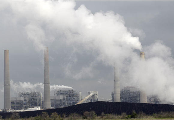 Exhaust rises from smokestacks in front of piles of coal at NRG Energy's W.A. Parish Electric Generating Station in Texas in 2011. The Environmental Protection Agency proposed new rules Thursday that would lower the amount of fine particulate matter, or soot, that enters the air from sources such as power plants and diesel engines.