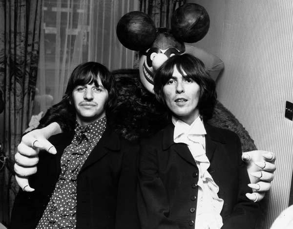 Ringo Starr and George Harrison pose with a 'Blue Meanie,' a character from their animated musical film 'Yellow Submarine.'