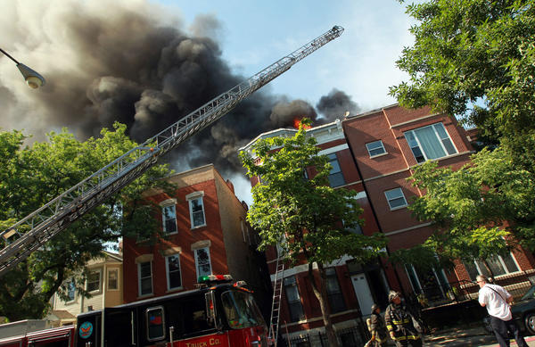Smoke billows from a blaze that damaged two buildings in the 1400 block of West Erie Street in Chicago this afternoon.