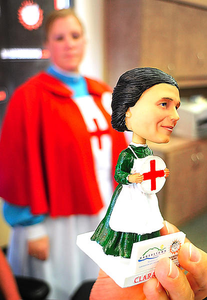 Clara Barton bobblehead is unveiled Friday at Hagerstown-Washington County Convention and Visitors Bureau. Bureau board of directors president Julie Rohm donned an early Red Cross nurses uniform for hte occasion.