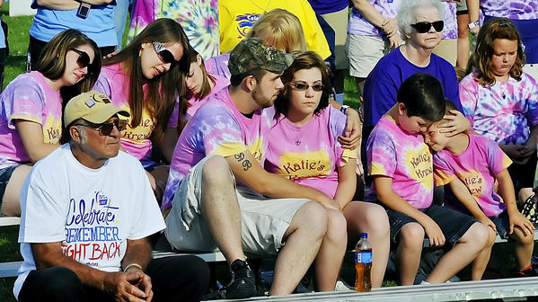 Friends and family of Katie Stains of Williamsport console each other as they listen to a song during the opening ceremonies of the Relay for Life.