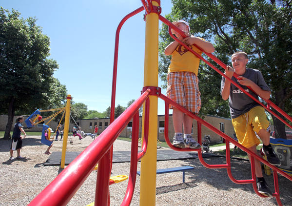 Camp DreamMakers volunteer Gus Reede, 13, of Aberdeen, right, climbs a piece of playground equipment with camper Gabe Smith, 11, of Langford, as they played Tuesday at the South Dakota School for the Blind and Visually Impaired. American News Photo by John Davis