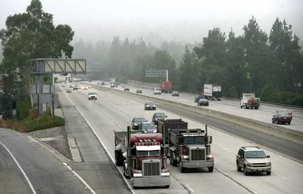 Freeeway traffic moves along the 210 Freeway through La Canada Flintridge at the St. Francis High School overpass. Officials plan to study the effects of building sound walls near potentially historic structures.
